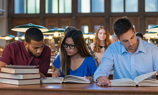 3 students studying in a library