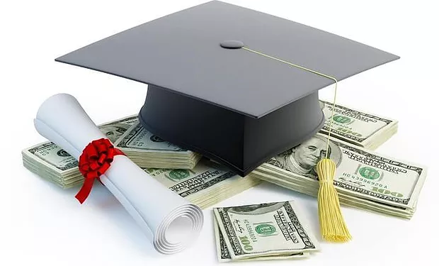 A graduation cap and a diploma sitting on top a pile of 100 dollar bills